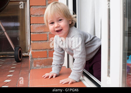 portrait of blonde caucasian baby nineteen month age chubby face looking at camera peering terrace floor supported - Stock Photo