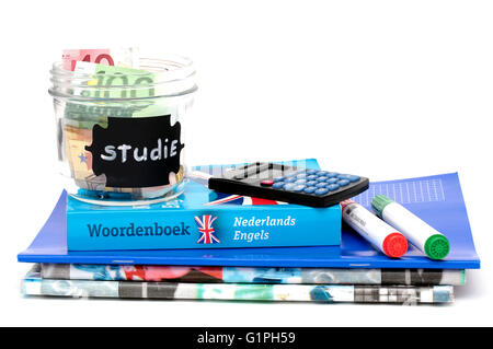 A jar filled with money, with the dutch word for study written on the label, on top of school books - Stock Photo