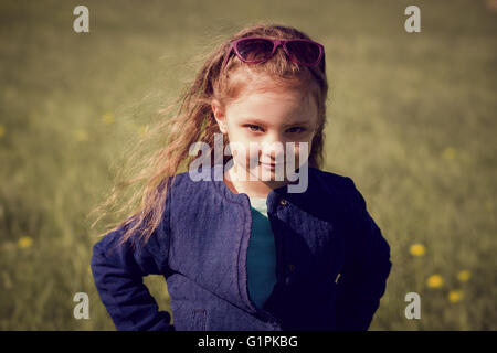 Fashion kid girl posing in blue jeans jacket on green grass spring background - Stock Photo