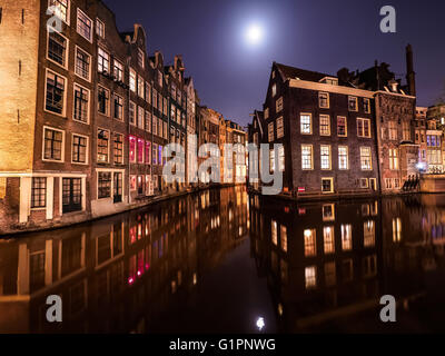 Amsterdam canals scene with water reflections and full moon. - Stock Photo