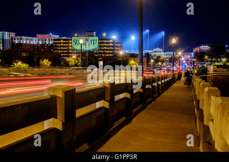 Downtown Oklahoma City life at night, showing light trails and people. Oklahoma, USA. - Stock Photo