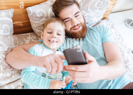 Top view of cheerful bearded father using smartphone and lying on bed with little son - Stock Photo