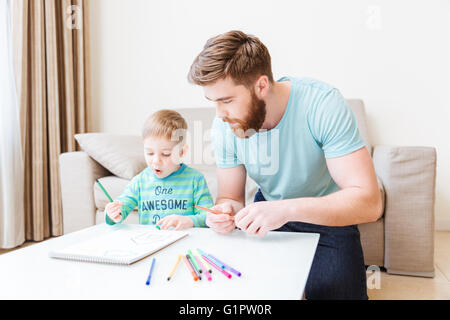 Father and son sitting and drawing in living room at home - Stock Photo
