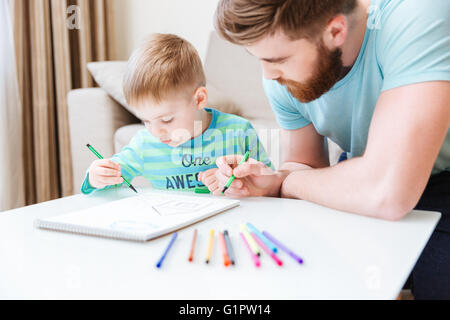 Son and dad sitting and drawing together on the table - Stock Photo