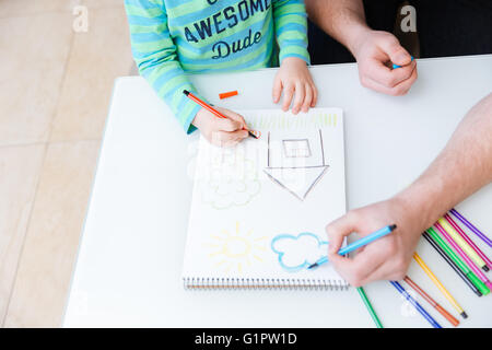 Top view of hands of little son and his father drawing with colorful markers on the table - Stock Photo