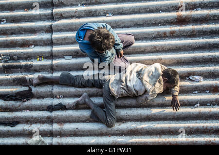 An image taken, at morning, down on two homeless children sleeping on a roof near a train station in Janwar, India. - Stock Photo