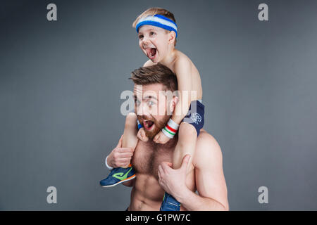 Closeup of father and his little son having fun and shouting over grey background - Stock Photo