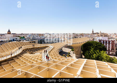 Tourists visiting the lookout on Metropol Parasol building at Seville, Spain, enjoying the view over the city - Stock Photo
