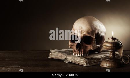 Human skull, lit candle and open ancient book on an old wooden table, knowledge and literacy concept - Stock Photo
