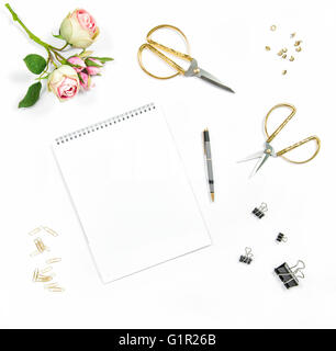 Flat lay with sketchbook, flowers, office tools on white background - Stock Photo