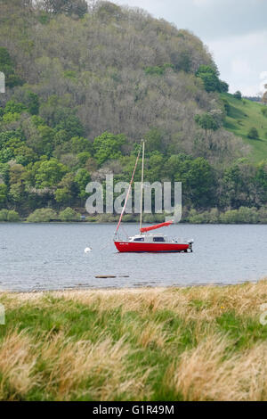 Red yacht on Ullswater in the Lake District - Stock Photo