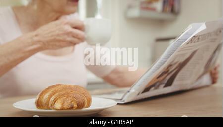 Senior woman drinking coffee - Stock Photo