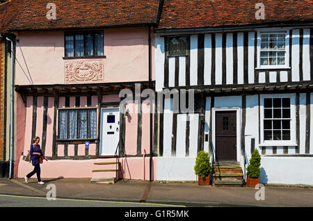 Woman walking past half-timbered houses in Lavenham, Suffolk, England UK - Stock Photo