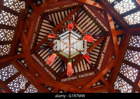 Geometric pattern of wooden beams in a Chinese gazebo ceiling with hanging lantern - Stock Photo