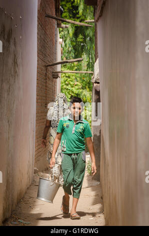 Young boy walks down an alleyway carrying a bucket of water in a village in Gujarat, India - Stock Photo