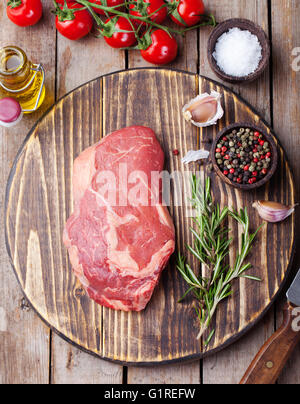 Raw fresh meat Steak with salt and pepper, rosemary and tomatoes on cutting board on dark wooden background Top - Stock Photo