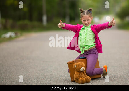 Funny little girl sitting on the road with a suitcase and a teddy bear. - Stock Photo