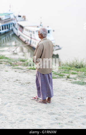 A man praying standing on the bank of the Irrawaddy river one evening just after the sunset in Bagan in Myanmar. - Stock Photo
