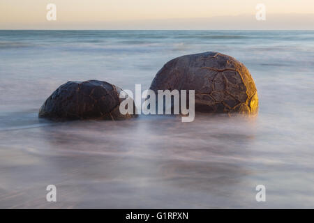 Moeraki Boulders on the Koekohe beach, New Zealand during sunrise (long exposure) - Stock Photo