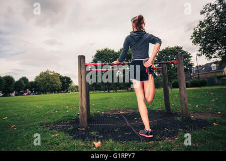 A young woman is stretching her legs on fitness equipment in the park - Stock Photo