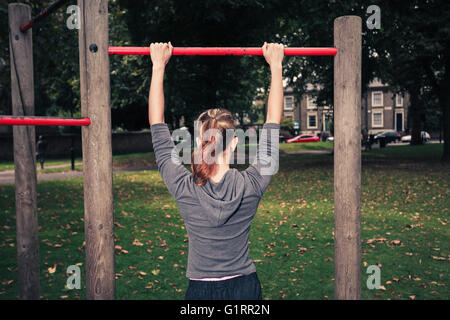 A young woman is doing pullups in the park - Stock Photo