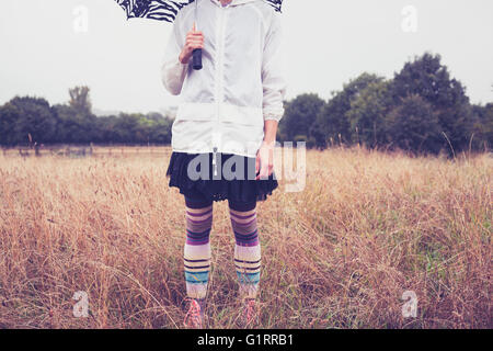 A young woman with an umbrella is standing in a field - Stock Photo