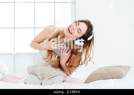 Funny woman listening music on tablet computer in the bed at home - Stock Photo