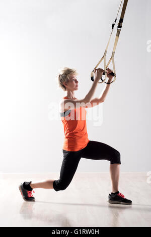 Single woman in orange and black exercise tights stretching and pulling on training rings - Stock Photo