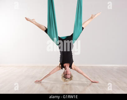 Single upside down woman doing aerial yoga splits with assistance of large green flexible tarp suspended from ceiling - Stock Photo