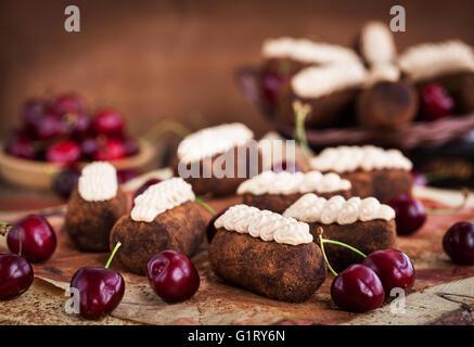 Chocolate rum balls cakes decorated with cream and fresh cherry - Stock Photo
