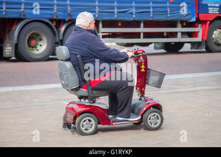 Senior, Pensioner disabled person using Powered Mobility scooter on the move on Blackpool promenade, Lancashire, - Stock Photo