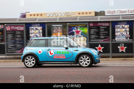 Mini vehicle in motion being driven along the seafront at Blackpool, Lancashire, UK. - Stock Photo