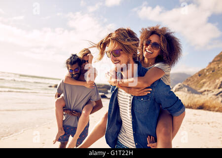 Two happy young men giving their girlfriends piggyback rides. Group of young people enjoying themselves during summertime - Stock Photo