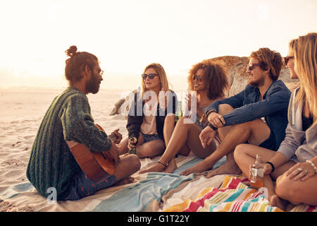 Group of friends relaxing at a sunset beach party with young man playing a guitar. Young people having a party on - Stock Photo