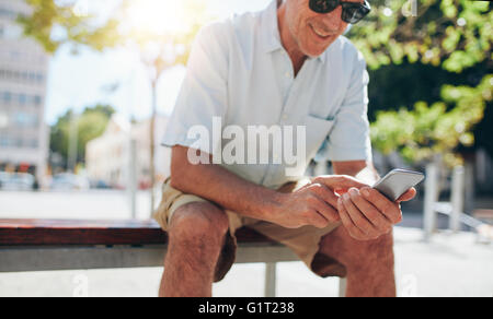 Cropped portrait of smiling mature man using mobile phone while sitting outdoors on a bench in the city - Stock Photo