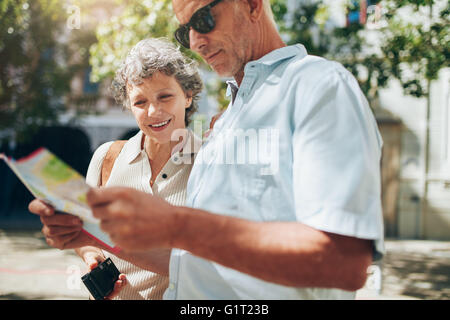 Close up shot of active senior on a vacation reading a city map. Mature man and woman using city map for directions - Stock Photo
