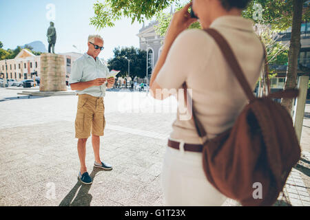 Senior man being photographer by a woman in the city during their vacation. Senior couple taking photos on their - Stock Photo