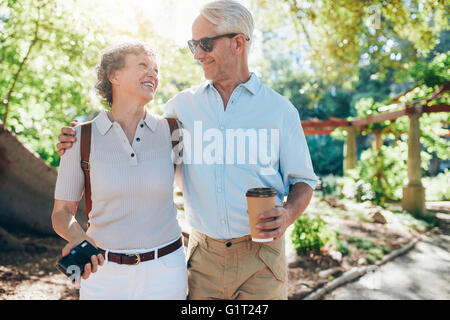 Portrait of happy mature couple walking together in a park. Husband and wife on a vacation. - Stock Photo