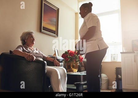 Senior woman sitting on a chair at home with female caregiver standing by. Female nurse visiting senior patient - Stock Photo