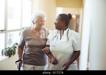 Senior woman walking in the nursing home supported by a caregiver. Nurse assisting senior woman. - Stock Photo
