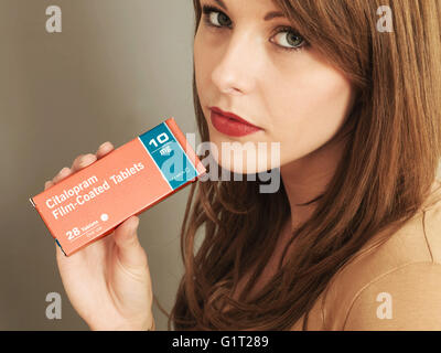 Portrait of a Woman Holding a Packet of Citalopram 10mg Tablets Looking Up at the Camera - Stock Photo
