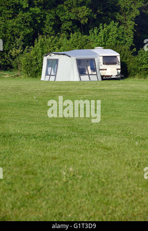 A single caravan with tent on a farm site. Space for text. - Stock Photo