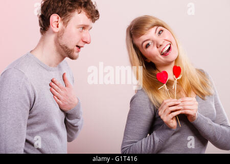 Togetherness in love. Attractive young smiling couple with little red hearts on sticks. Woman and man having good - Stock Photo