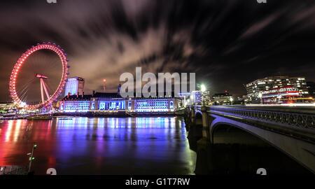 London Eye and Bridge across water at night time. Long exposure
