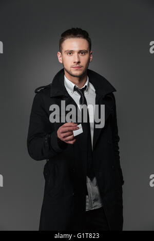 Confident young businessman in black coat giving you blank business card over grey background - Stock Photo