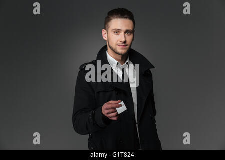 Handsome young businessman in black coat, white shirt and tie giving blank business card over grey background - Stock Photo