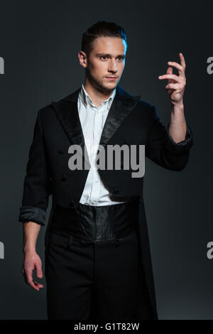Serious young man magician in black tail coat standing with raised hand and showing tricks over grey background - Stock Photo