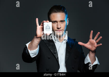 Confident young man magician showing ace card over grey background - Stock Photo