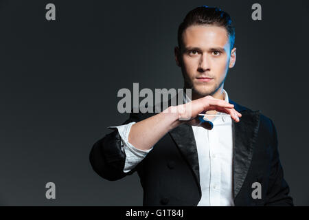 Handsome young man magician showing tricks with playing cards over grey background - Stock Photo