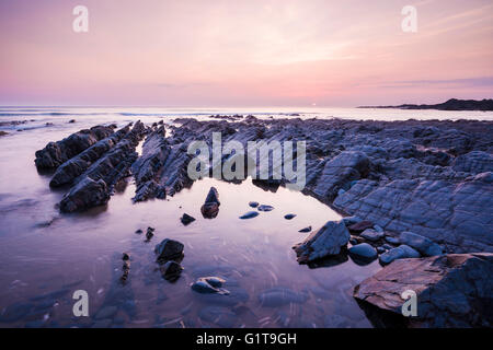 The rocky shore at Speke's Mill Mouth on the North Devon coast at sunset near Hartland, England. - Stock Photo